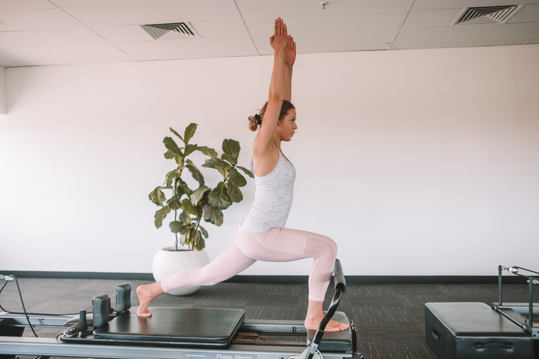 Instructor demonstrate an exercise on a reformer