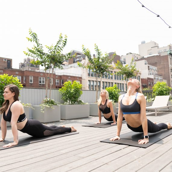 Member practicing yoga on the roof